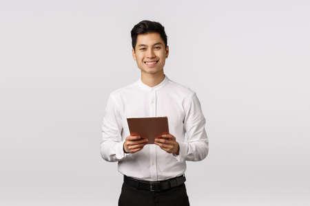 Foto de Cheerful, polite handsome elegant asian guy in white shirt, black pants, holding digital tablet and smiling camera, using gadget for work, messaging using device, shopping online, white background - Imagen libre de derechos