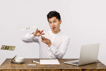 Foto de Time to party. Carefree wealthy and successful young chinese male entrepreneur, throwing money at camera with sassy delighted expression, wasting cash, playing with dollars, white background - Imagen libre de derechos