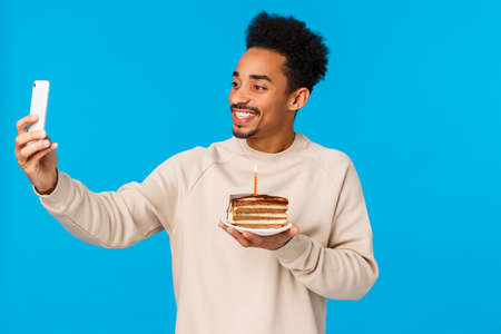 Photo pour Celebration and holidays concept. Cheerful african american guy addicated social media, sharing memory with online followers, holding b-day cake with candle, taking selfie, celebrate birthday. - image libre de droit
