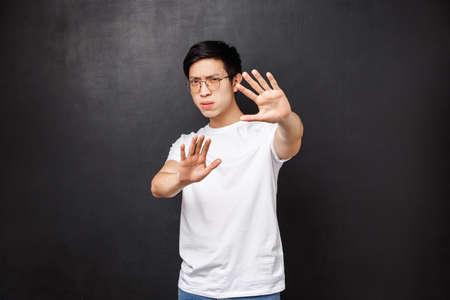 Photo pour Serious-looking annoyed and displeased asian guy telling stop it, cover face with hands as if defending himself from glimmering light, squinting bothered with too bright lamp, black background - image libre de droit