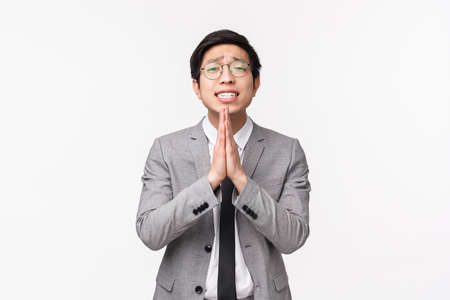 Photo for Waist-up portrait of hopeful desperate asian office worker, man begging for coworker cover him at work, press hands together in pray and shaking them say please, pleading over white background - Royalty Free Image