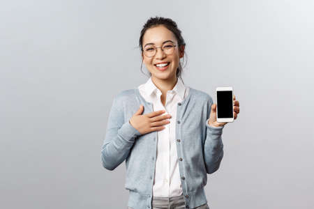 Photo pour Technology, online and mobile lifestyle concept. Happy boastful asian woman showing pictures or her profile on app smartphone display, holding phone laughing and smiling camera pleased - image libre de droit