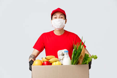 Photo for Online shopping, food delivery and coronavirus pandemic concept. Smiling delivery man in red uniform, holding box with fresh groceries, wear medical mask and gloves, contactless shopping - Royalty Free Image