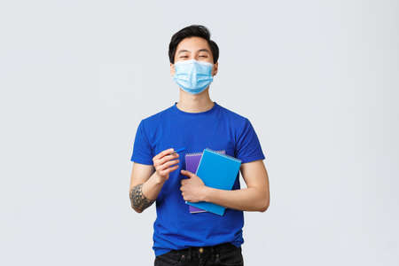 Photo pour Back to school, studying during covid-19, education and university life concept. Handsome carefree asian male student, college guy in medical mask holding notebooks and smiling - image libre de droit