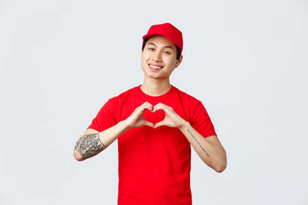 Express delivery, shipping and logistics concept. Friendly handsome asian courier in red cap and t-shirt, company uniform, show heart gesture and smiling delighted, care for customers and clients