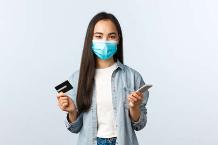 Photo pour Social distancing lifestyle, covid-19 pandemic and contactless shopping concept. Pretty smiling asian female in medical mask, paying for online order using mobile phone and credit card - image libre de droit