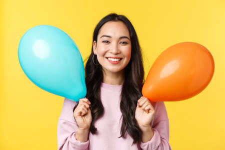Foto de People emotions, lifestyle leisure and beauty concept. Happy cute asian birthday girl celebrating big event, holding balloons congratulating with holidays, standing yellow background - Imagen libre de derechos