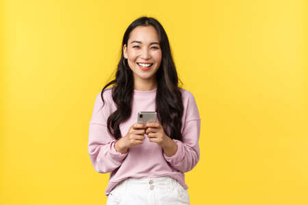 Foto de People emotions, lifestyle leisure and beauty concept. Happy and surprised pretty korean girl in stylish outfit, looking amazed with broad smile camera after reading great news in mobile appplication - Imagen libre de derechos