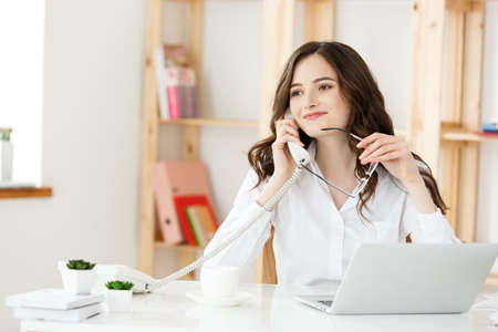 Photo pour Young attractive woman at a modern office desk, working with laptop and thinking about something. - image libre de droit