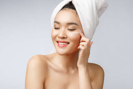 Photo pour health and beauty concept - Attractive asian woman applying cream on her skin, isolated on white. - image libre de droit