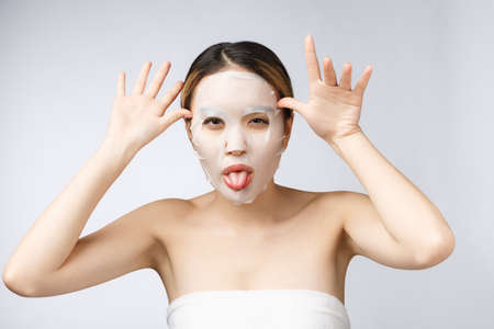 Photo for Spa, healthcare. Asian girl with a cosmetic mask isolate on white. - Royalty Free Image