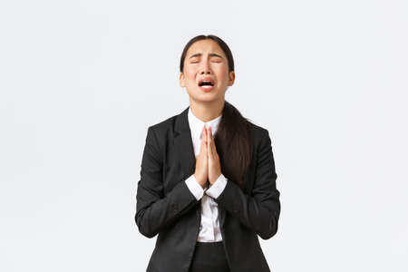 Photo for Overworked and distressed asian businesswoman begging for help, screaming hold hands together, pleading and crying desperate, standing upset over white background - Royalty Free Image