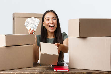 Photo for Small business owners, startup and e-commerce concept. Smiling asian woman showing money and giving box with order, selling online, earn cash for internet store, shipping handmade products - Royalty Free Image