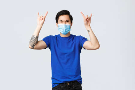 Different emotions, social distancing, self-quarantine on covid-19 and lifestyle concept. Carefree good-looking asian guy having fun home, show rock-n-roll sign as listening music