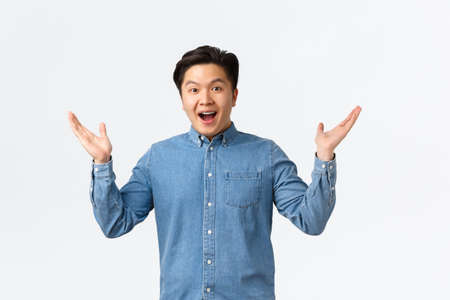 Photo pour Happy and excited asian surprised guy receive awesome news, raising hands sideways and smiling amazed, praising great job, saying congrats, rejoicing over white background - image libre de droit