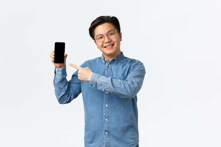 Photo pour Smiling handsome asian guy with braces and glasses, pointing finger at smartphone screen. Man showing promo or application on mobile phone display, promote site, standing white background - image libre de droit