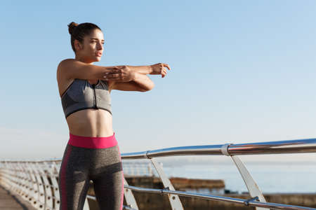 Foto für Image of determined female runner stretching on the seaside promenade before jogging. Girl warming-up on pier to start workout, looking at the sea - Lizenzfreies Bild