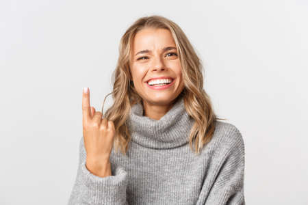 Photo for Close-up of carefree blond girl in grey sweater, showing one finger and smiling, standing over white background - Royalty Free Image