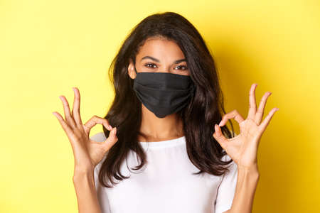 Photo for Concept of coronavirus, pandemic and lifestyle. Close-up of confident, smiling african-american woman in black face mask, showing okay signs in approval, like something good, yellow background - Royalty Free Image