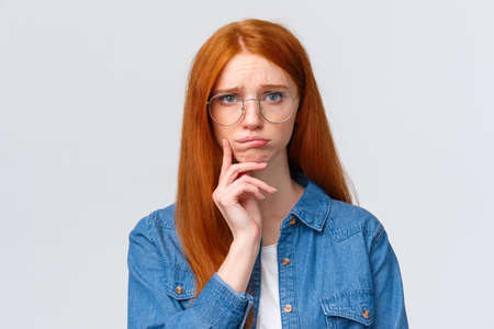 Photo pour Uneasy, indecisive timid cute redhead girl dont know what do in future, deciding what college enter, having troubled with making choice, pouting and looking camera gloomy - image libre de droit
