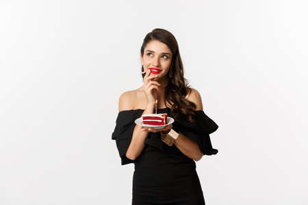 Photo for Celebration and party concept. Dreamy woman in black dress making wish, thinking and holding birthday cake with candle, standing over white background - Royalty Free Image
