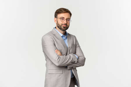 Photo pour Portrait of confident businessman with beard, wearing grey suit and glasses, cross arms on chest and smiling self-assured, standing over white background - image libre de droit