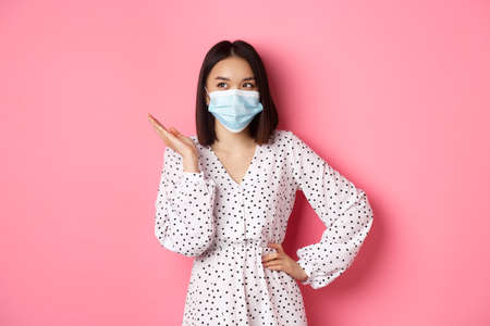 Photo pour Covid-19, quarantine and lifestyle concept. Lovely asian woman in face mask raising hand, standing in dress over pink background - image libre de droit