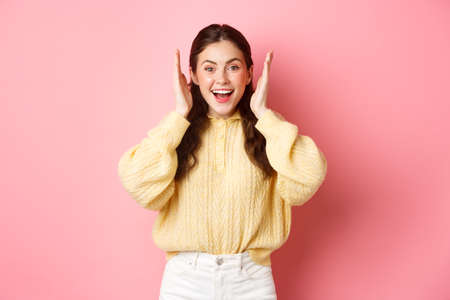 Photo pour Cheerful young woman smiling, looking excited, open her ears after loud bang or fireworks, celebrating something, standing against pink bright background - image libre de droit