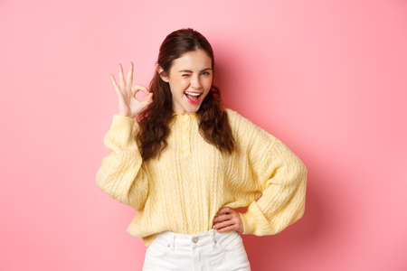 Photo pour Cheeky young woman winking, showing okay sign, give her approval, like and approve good thing. Girl make OK gesture to give permission, say yes, standing over pink background - image libre de droit