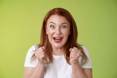Photo for Close-up lucky enthusiastic cute redhead joyful middle-aged woman pump fists vigorous excitement celebratory smiling broadly winning celebrating triumphing success good news green background - Royalty Free Image