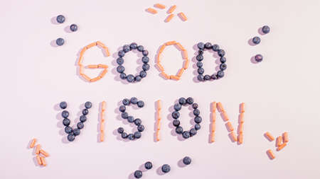 Photo pour Vitamins and supplements for healthy eyes on pink background. How to maintain good vision concept. Blueberry and orange capsules forming words good vision - image libre de droit