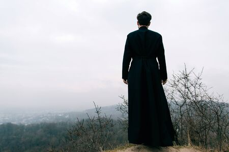 Photo pour Portrait of handsome catholic bearded man priest or pastor posing outdoors in mountains - image libre de droit
