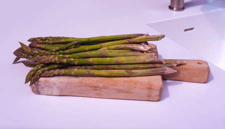 View of bunch of fresh asparagus on cutting board