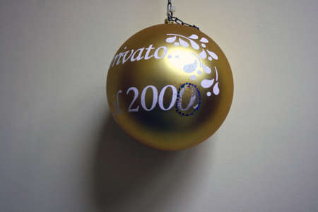 Photo pour Old gold christmas ball dated 2000 on the gray wall - image libre de droit