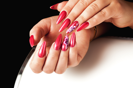 Acrilyc red nails on hands and floral deign.の写真素材