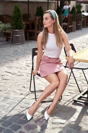 Photo for Young beautiful girl dressed in retro vintage style in the old european city sitting on the street cafe wooden table - Royalty Free Image