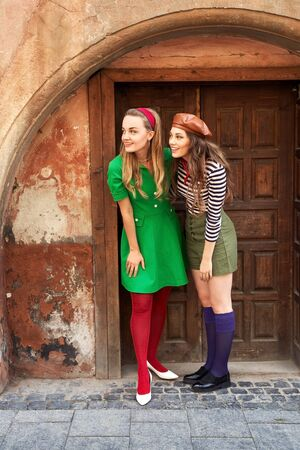Photo for Young beautiful girls dressed in retro vintage style enjoying the old european city lifestyle while looking surprised - Royalty Free Image