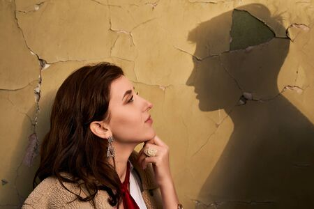 Photo pour Beautiful young redhead woman wearing teddy jacket and white shirt and red neckpiece is thinking of her ideal boyfriend man or lover represented by a shadow on the wall - image libre de droit