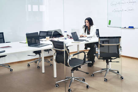 Photo pour Thoughtful confident caucasian business woman or manager alone in modern office. Lady is sitting at table in meeting room of a software development company or technology startup. - image libre de droit