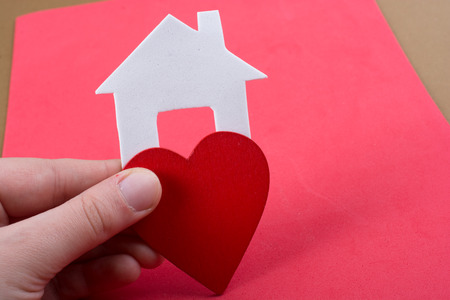 Photo pour Little house cut out of paper and a heart in hand in view - image libre de droit