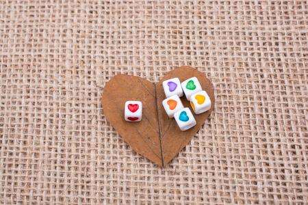Photo pour Colorful cubes with a heart  on leaf on canvas - image libre de droit