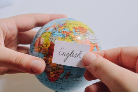 Hand holding notepaper with English wording on model globe