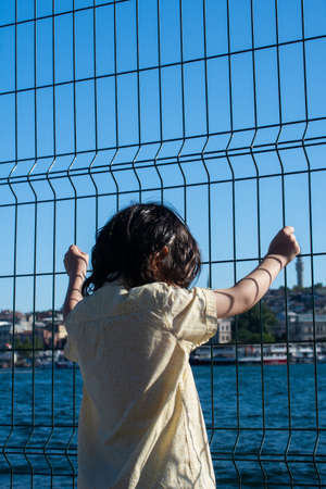 Thoughtful little  boy with Istanbul mosque  panorama behind the fence