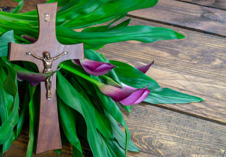 Photo for Cross with jesus christ on a wooden background with a purple calla - religious easter lent concept background - Royalty Free Image