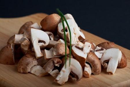 heap of chopped mushrooms on a wooden board