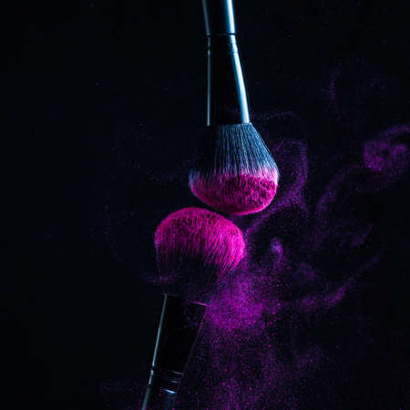 Photo for Cosmetic Brushes And Explosion Colorful Powders. Colorful explosion under makeup. - Royalty Free Image