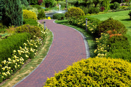 Photo for a curved path of paving slabs in a park area with landscape design and a flower bed with blooming roses and bushes. - Royalty Free Image