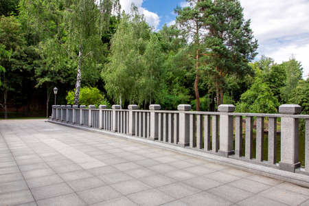 Photo for view of a bridge with stone tiles and granite railings with square columns on background a park with green trees and sky, nobody. - Royalty Free Image
