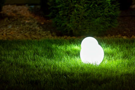Photo for backyard garden light with lantern electric lamp with sphere diffuser in green grass with thuja bushes and stone mulching in park with landscaping, closeup night scene nobody. - Royalty Free Image