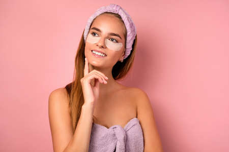 Photo pour Portrait of a smiling girl with a bandage on her head, in a lilac towel and with patches under eyes, dreamily looking to the side - image libre de droit